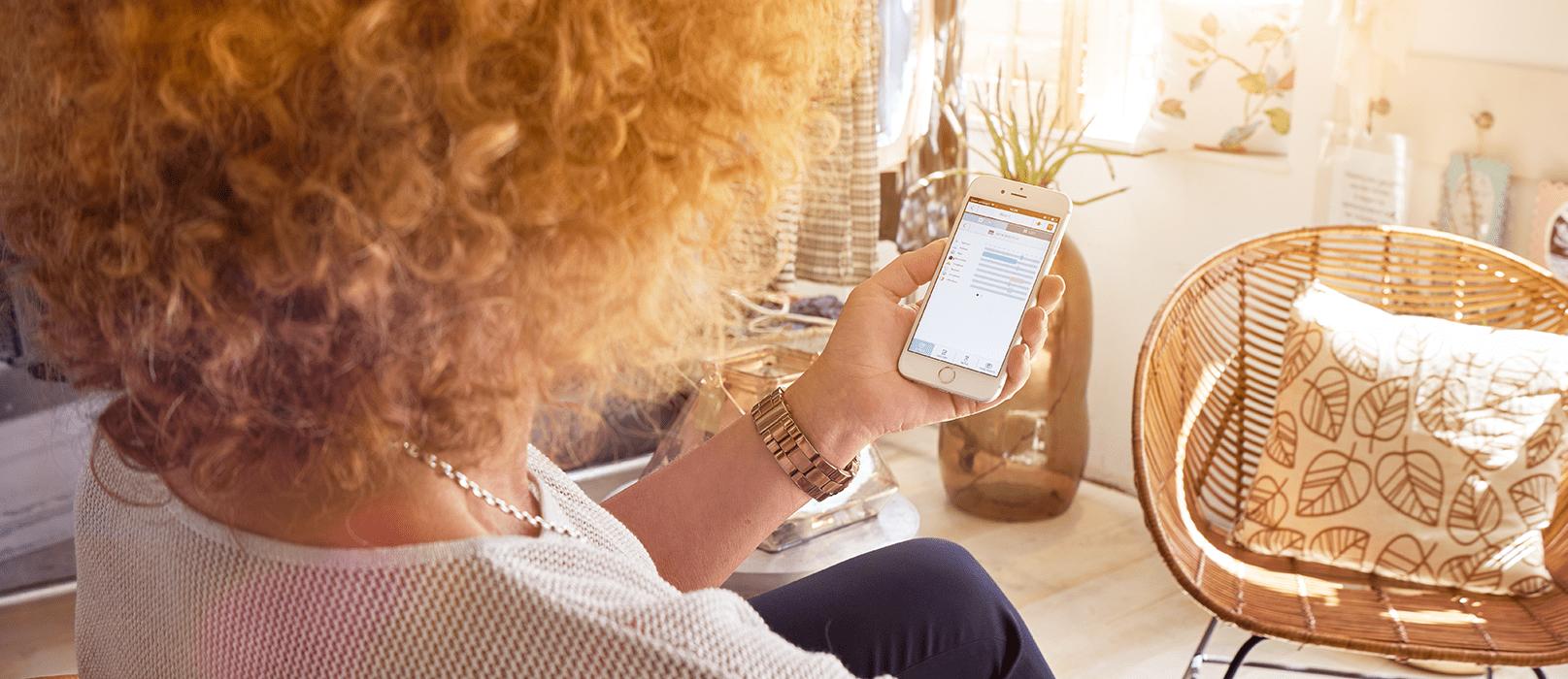 Mantelzorger checkt cAlarm Sense op haar smartphone