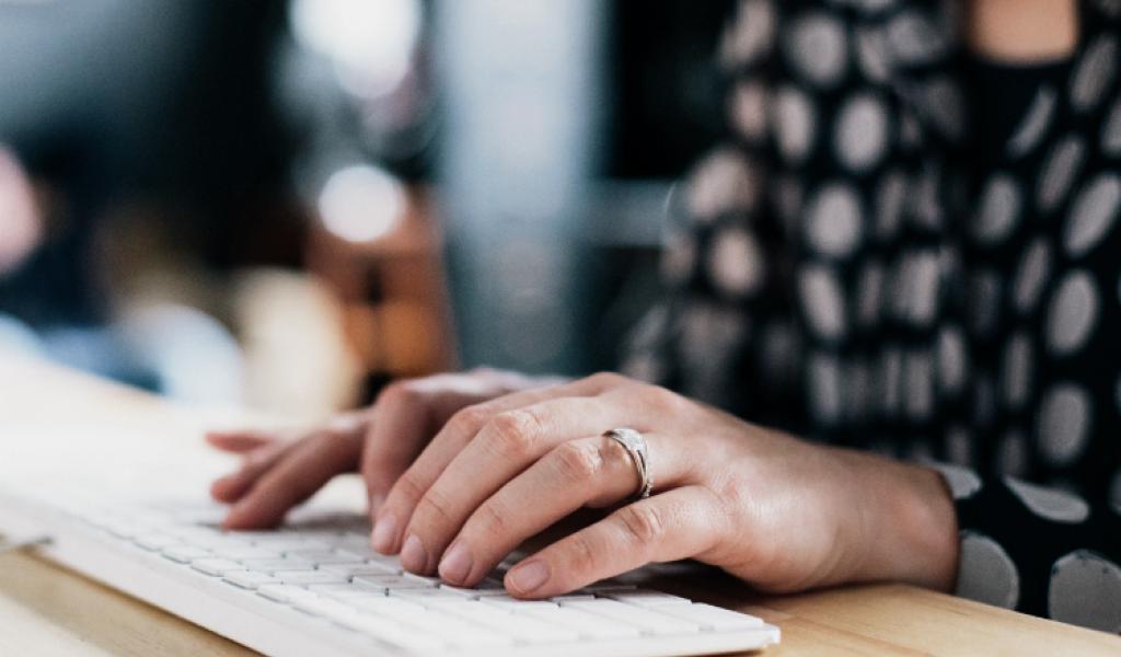 Een vrouw typt een vraag naar de FocusCura klantenservice