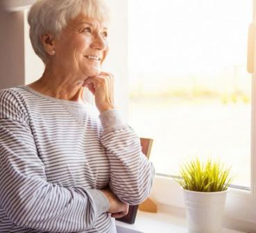 Uit het raam kijkende vrouw met personenalarmering